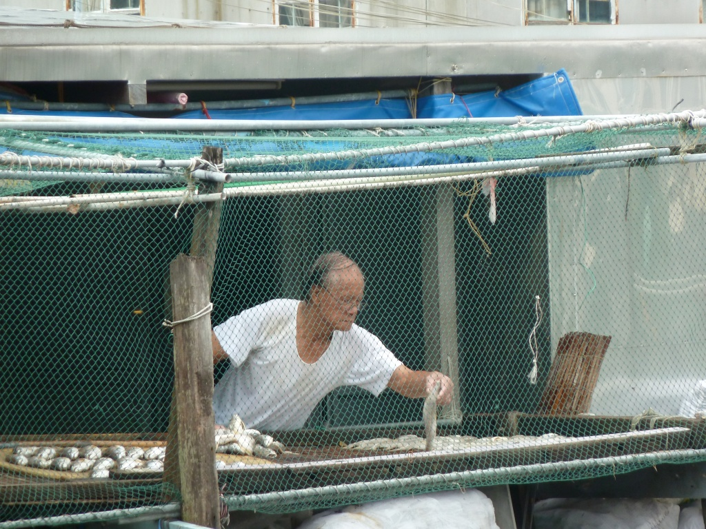 Old Man laying out fish Tai O Fishing Village Hong Kong LisaDeviAdventures